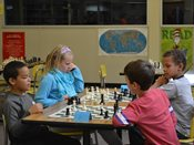 Students playing chess at chess tournament