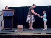 Author receives his award and booklet on stage.