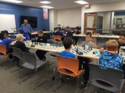 Chess Tournament: Students playing chess at tables.